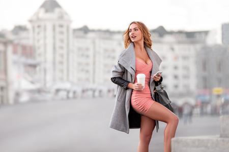 taza cafe: Una mujer de negocios con un teléfono móvil con una taza de café contra la escena urbana. Foto de archivo