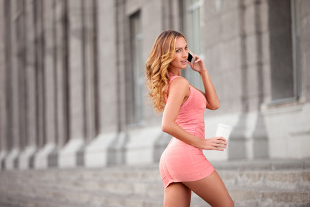 breakfast cup: A pretty woman in a pink dress using mobile phone and holding a take away coffee. Stock Photo