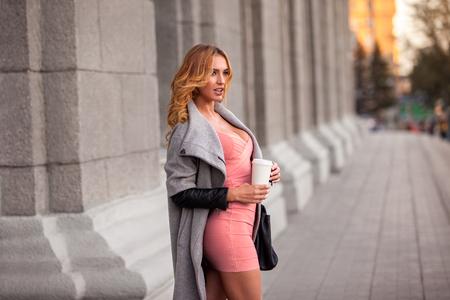 Eine hübsche Frau mit einem Kaffee gegen den städtischen Szene zu gehen.
