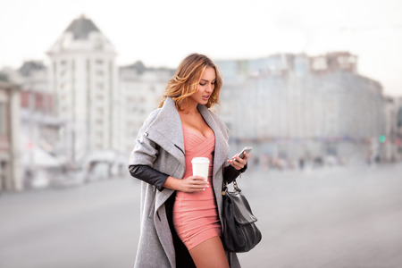 style woman: A businesswoman checking email via mobile phone and holding a coffee cup against urban scene.