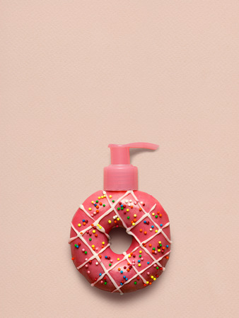 Creative still life of a tasty sweet strawberry donut with a cosmetic pump dispenser on pink background. Stock Photo