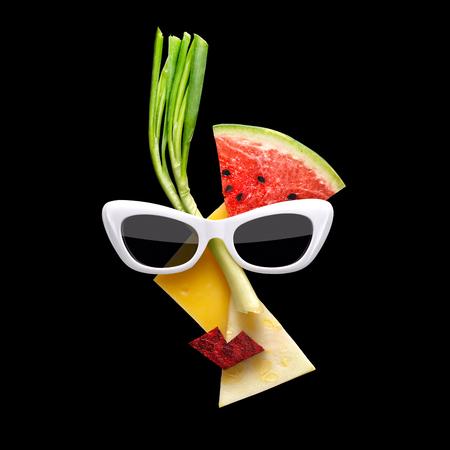 Concepto de comida peculiar de la cara femenina de estilo Picasso en gafas de sol hechas de frutas frescas en el fondo negro.