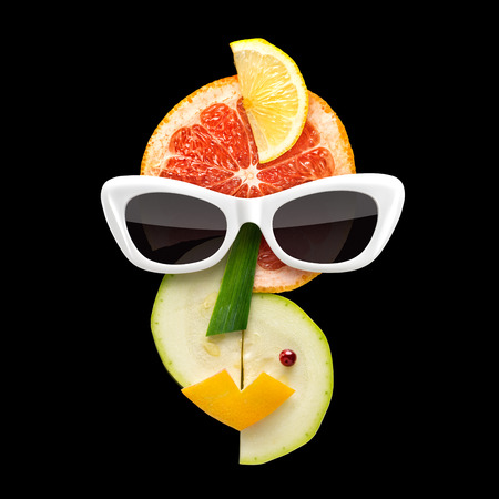 picasso: Quirky food concept of Picasso style female face in sunglasses made of fresh fruits on black background.