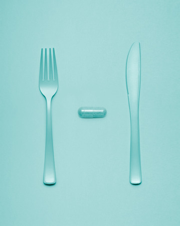 lunchtime: Creative still life of fork and knife at a lunchtime with a pill served. Stock Photo