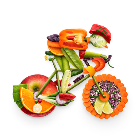 Healthy food concept of a cyclist riding a bike made of fresh vegetables and fruits, isolated on white.