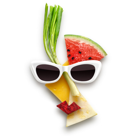 Quirky food concept of Picasso style female face in sunglasses made of fruits and vegetables, isolated on white.