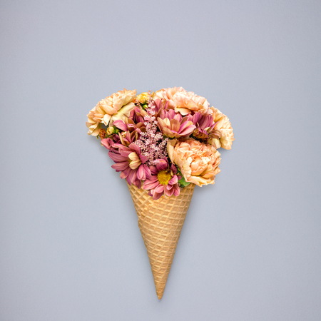 olfato: Creative still life of an ice cream waffle cone with flowers on grey background.