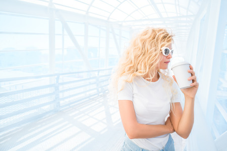 Thoughtful blonde young woman in sunglasses with take away coffee cup posing on the urban bridge. Stock Photo