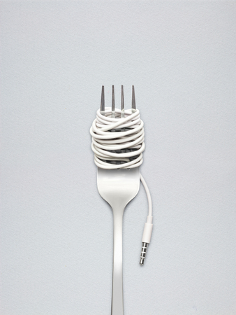 unhealthy thoughts: A shining fork with noodle made of cable with music jack plug in metal background.