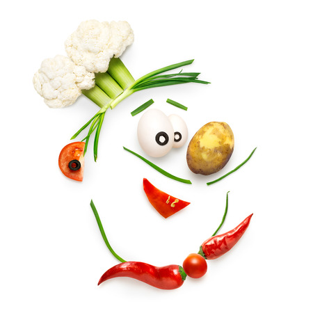 cuisine entertainment: Creative food concept of a funny cartoon chef face made of vegetables isolated on white. Stock Photo