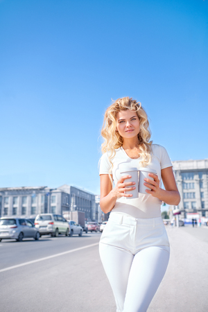 Beautiful young woman with two takeaway coffee cups, standing against urban city background and looking aside.