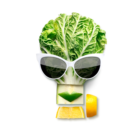 Quirky food concept of cubist style female face in sunglasses made of fruits and vegetables, isolated on white.