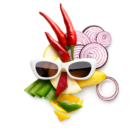 quirky: Quirky food concept of cubist style female face in sunglasses made of fruits and vegetables, on white. Stock Photo