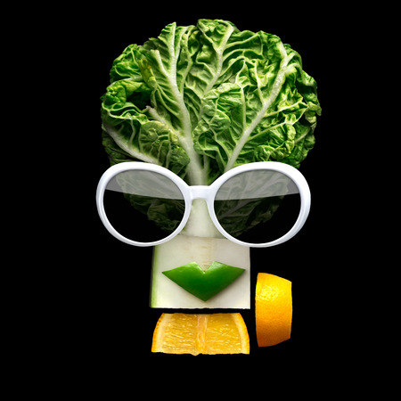 Quirky food concept of cubist style female face in sunglasses made of fresh fruits on black background. Stock Photo