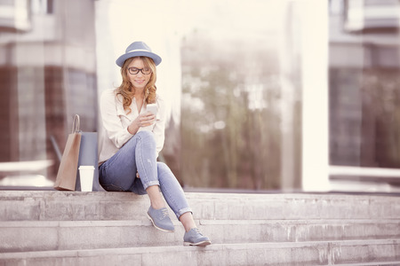 go shopping: Happy young woman with a disposable coffee cup and shopping bags sitting on the stairs and using her smartphone for communication via wifi internet in a summer park. Stock Photo