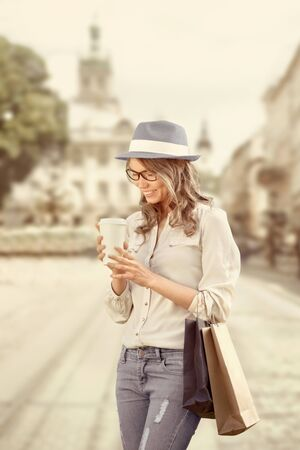 Happy young fashionable woman with shopping bags enjoying drinking coffee after shopping and holding take away coffee against urban background. Stock Photo
