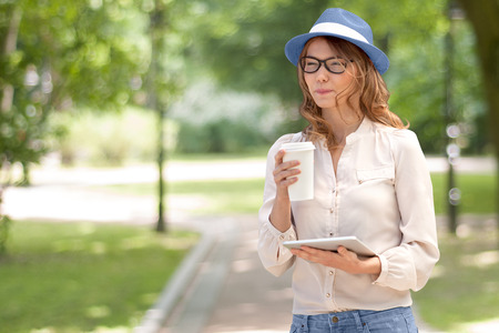Happy young woman with a disposable coffee cup, holding tablet in her hands, drinking coffee and smiling against summer park background.