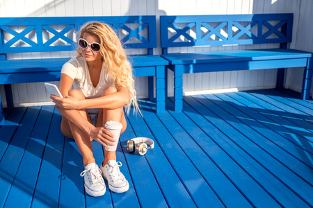 Beautiful young woman with a take away coffee cup holding a mobile phone and music headphones near her, sitting near the bench and waiting for a water taxi at the station.