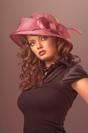 bonnet up: A portrait of a sexy brunette wearing a black retro dress and a rosy designer hat with a bow.