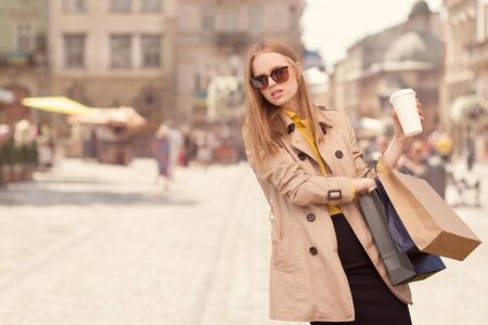 go shopping: Young fashionable woman taking a coffee break after shopping, walking with a coffee-to-go in her hands against urban city background. Stock Photo