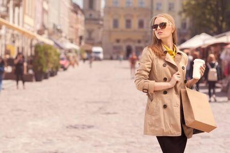 Junge moderne Frau, die eine Kaffeepause nach dem Einkaufen nehmen, mit einem Coffee-to-go zu Fuß in den Händen gegen den städtischen Stadt Hintergrund.