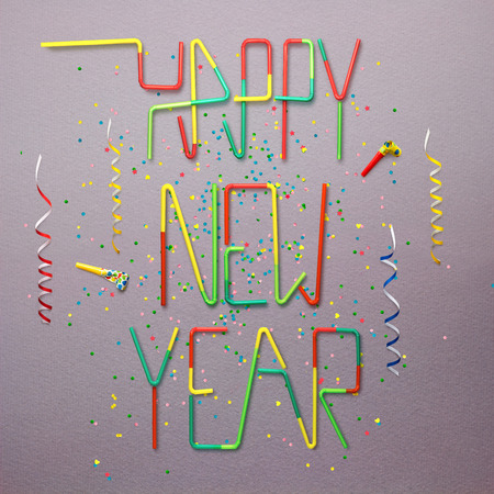 photo: Creative still life photo of happy new year sign made of cocktail straws with confetti and serpentine on grey background.