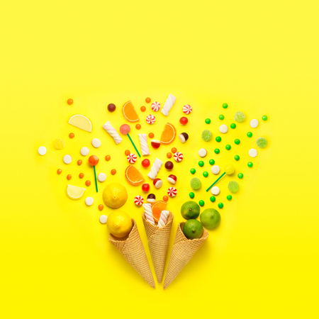 Creative still life photo of three waffle cones with candies, fruits and marshmallow on jellow background.