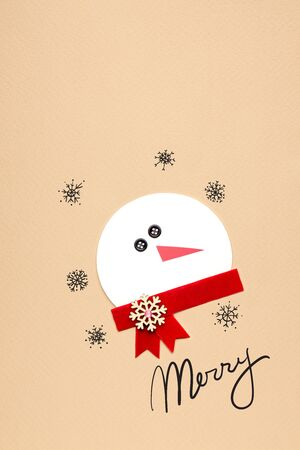 Creative photo of a snowman mad of paper on brown background.