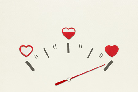 love life: Creative valentines concept photo of speedometer with hearts on grey background.