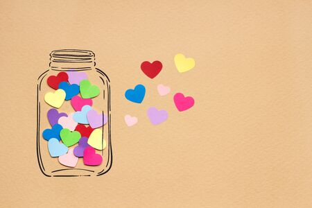 romance: Creative valentines concept photo of hearts in illustrated bottle on brown background.