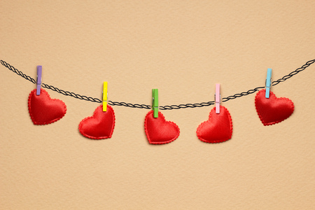 pinned: Creative valentines concept photo of hearts pinned on the rope on brown background. Stock Photo