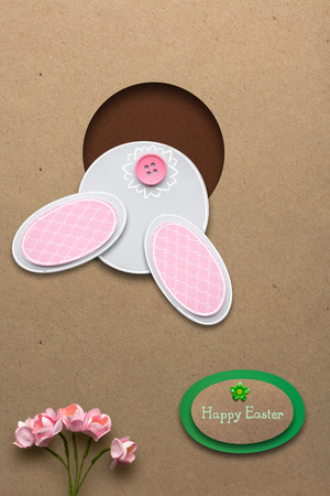 photo: Creative easter concept photo of a rabbit in a hole made of paper on brown background.