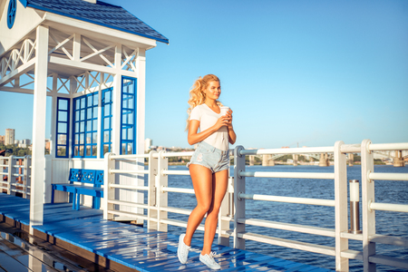 Beautiful young woman with a take away coffee cup, standing on the bridge near the water.