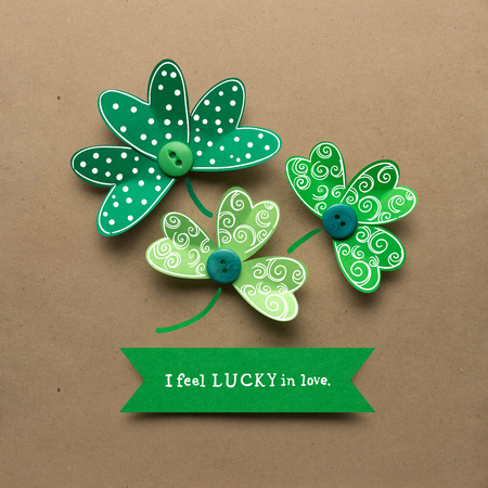 saint: Creative St. Patricks Day concept photo of shamrocks made of paper on brown background. Stock Photo