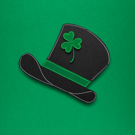 Creative St. Patricks Day concept photo of a leprechauns hat made of paper on green background. Stock Photo