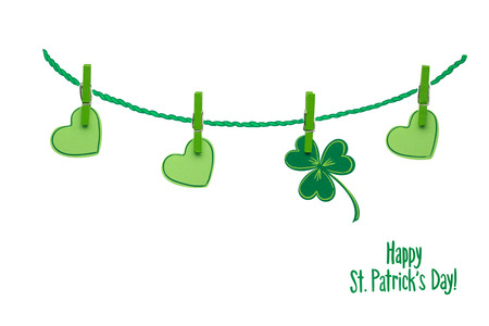 Creative St. Patricks Day concept photo of pinned  shamrocks and hearts made of paper on white background. Stock Photo
