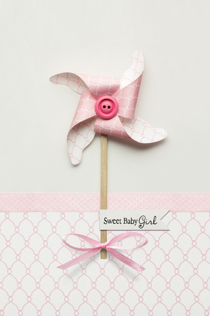 Creative concept photo of a wind mill made of paper on grey pink background. Stock Photo