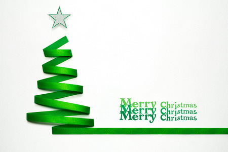 photo: Creative concept photo of christmas tree made of ribbon on white background.