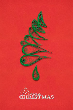Creative concept photo of a christmas tree made of paper on red background. Stock Photo