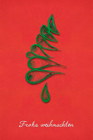 Creative concept photo of a christmas tree made of paper on red background. Frohe Weihnachten. Stock Photo