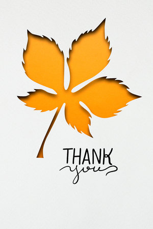 greeting season: Creative thanksgiving day concept photo of a leaf made of paper on white background.