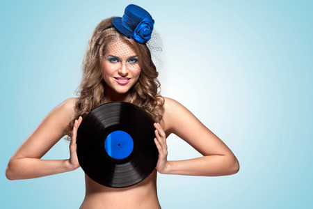 The vintage photo of girl in vintage hat holding vinyl record.