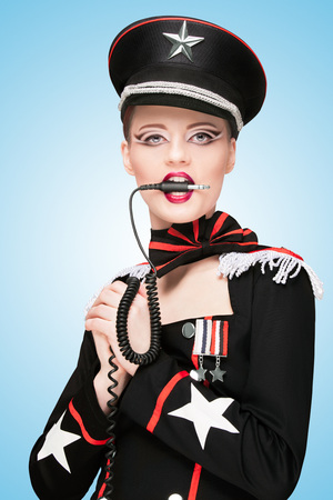 Sexy girl, dressed in a military uniform dress like a dominatrix, biting vintage unplugged music headphones on blue background.