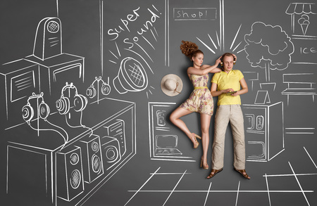 smartphone: Love story concept of a romantic couple against chalk drawings background. Male listening to the music in the headphones and surfing internet, female trying to gain his attention.
