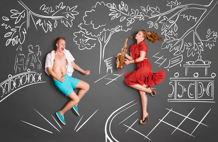 two: Love story concept of a romantic couple against chalk drawings background. Woman playing serenade on saxophone in a city park for her lover.