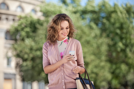 big: A beautiful woman using wireless internet and checking email via mobile phone in a big city.