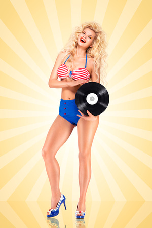 Mooie pinup bikini model, die een LP vinyl record op kleurrijke abstracte cartoon stijl achtergrond. Stockfoto