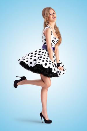 Creatieve vintage foto van een verlegen lachende pin-up girl draagt ??een retro polka-dot jurk en houdt haar jurk met beide handen, op een blauwe achtergrond.