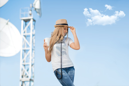 wave: Happy young woman in hat wearing vintage music headphones around her neck, drinking takeaway coffee and posing against background of parabolic satellite dish that receives wireless signals from satellites.