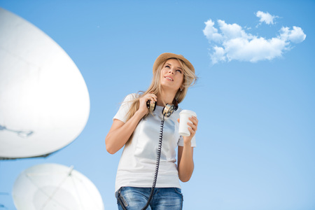 Happy young woman in hat wearing vintage music headphones around her neck, drinking takeaway coffee and posing against background of parabolic satellite dish that receives wireless signals from satellites.